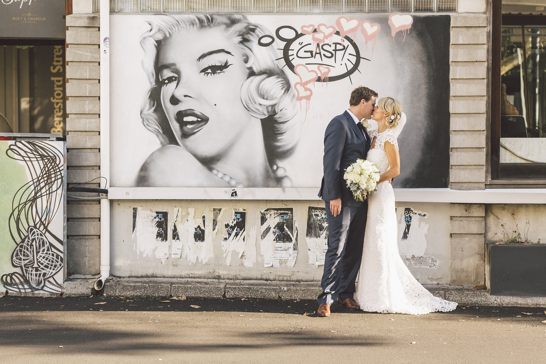 Bride and Groom in front of graffiti with large poster of Marilyn Monroe at a wedding where Diane was the celebrant